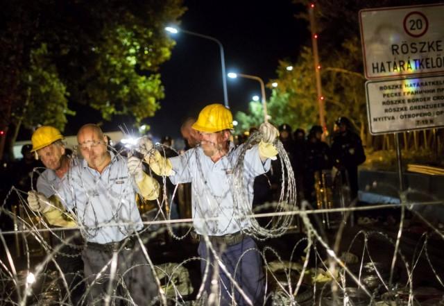 Az ideiglenes biztonsági határzárat erősítik meg a lezárt Röszkén. Fotó: Mohai Balázs, MTI