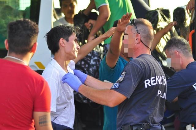 A migránsok szállítás előtt ruházat- és csomagátvizsgáláson esnek át. Fotó: Kacsúr Tamás